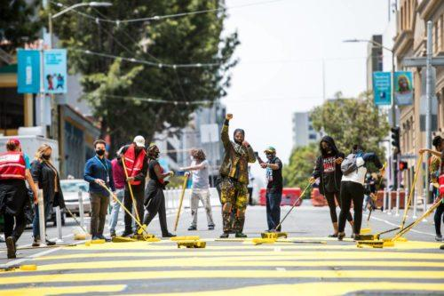 """Artist Malik Seneferu holds up his fist during the installation of a mural on Golden Gate Avenue in the Tenderloin that says """"Housing Black"""" on Aug. 10, 2020."""